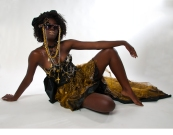 Ferosha Coutura is the quintessential image of the bad-ass amazonian goddess. Rocking a hand beaded sweetheart corset with a three tiered silk taffeta, printed silk chiffon, and iridescent gold silk organza skirt. Accented with a pair of crystal encrusted sunglasses that feature a zipper flower and a ton of chain. Second place recipient of the Drama Teachers Association of Southern California Costume Design Category 2009