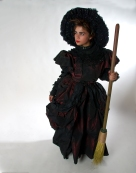 """Version 1; the Wicked Witch of the West. With references dating back to the let 1800's, this burgundy and black silk taffeta gown captures the true meaning of the word """"wicked."""" Her fully hand beaded pointed hat redefines the classic look."""